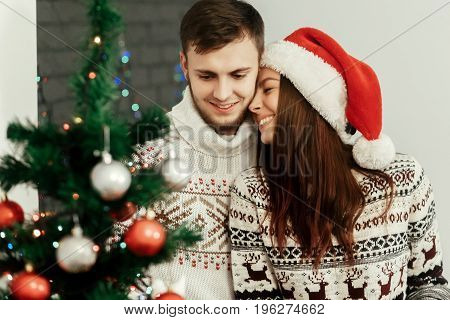 Stylish Happy Couple Decorating Christmas Tree. Fun True Emotions. Joyful Cozy Moments In Winter Hol