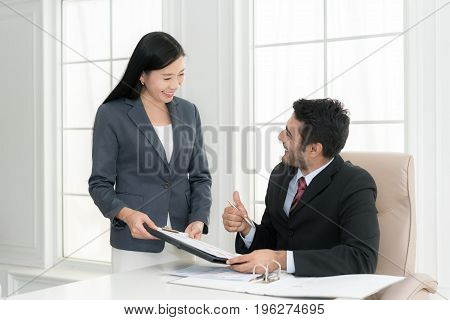 Asian businessman and his assistant Secretary in his office. The Secretary brought the boss documents to signBoss signs at documents and thumb up.