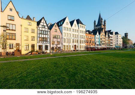 Houses and park in Cologne Germany. Many of them are colourful they are facing a public park with green grass and some trees. There is a Cologne bell tower on background. Travel and architecture concepts in Germany.