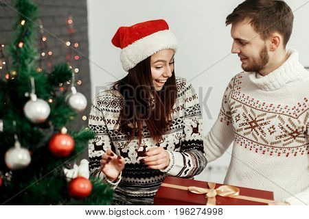 Surprised Happy Woman Receiving Big Present From Her Husband. Joyful Cozy Moments In Winter Holidays