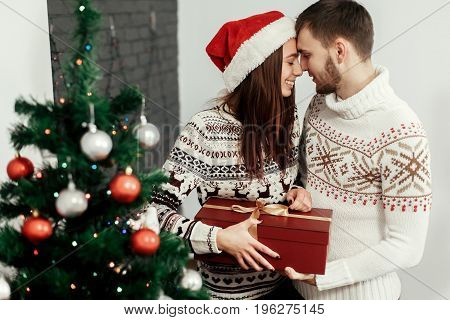 Stylish Happy Couple With Big Red Present Smiling Gently Hugging At Decorated Christmas Tree. Joyful
