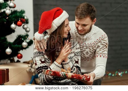 Man Giving Present To His Woman. Joyful Cozy Moments In Winter Holidays. Happy Stylish Family Smilin