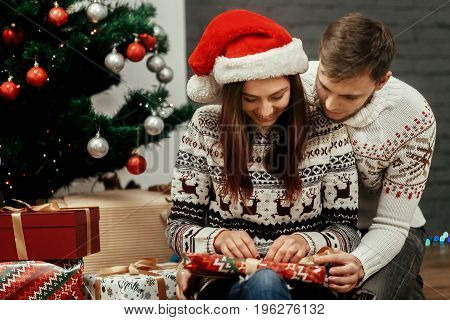Happy Smiling Brunette Girlfriend In Red Santa Hat Unwrapping Christmas Present From Her Handsome Bo