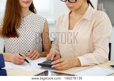 Two female accountants counting on calculator income for tax form completion hands closeup. Internal Revenue Service inspector checking financial document. Planning budget, audit concept.