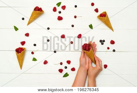 Top view of sweet fresh organic raspberries in waffle cones and one cone in girl's hands. Fresh berries in cones and on white wooden background. Summer and healthy food concept
