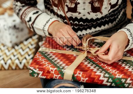 Beautiful Girl In Reindeer Winter Sweater Unwrapping Christmas Present With Golden Ribbon, Hands Clo