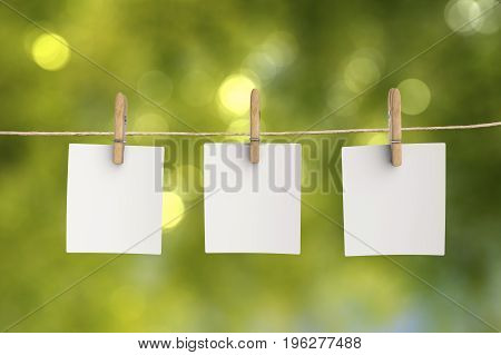 three blank papers hanging with cloth pegs