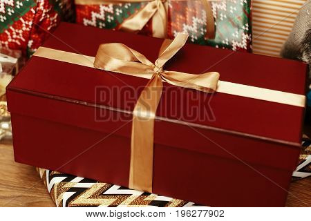 Luxury Big Red Present Box With Golden Ribbon On Background Of Stacked Stylish Gifts Under Beautiful