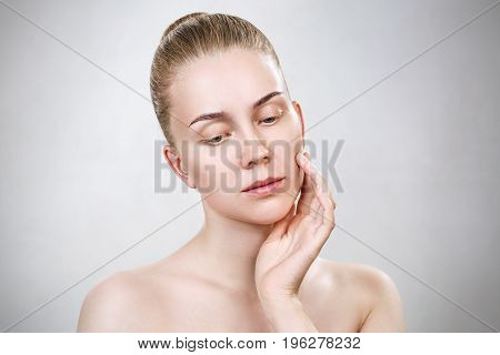Beautiful young woman with clean skin without make-up. Over gray background.