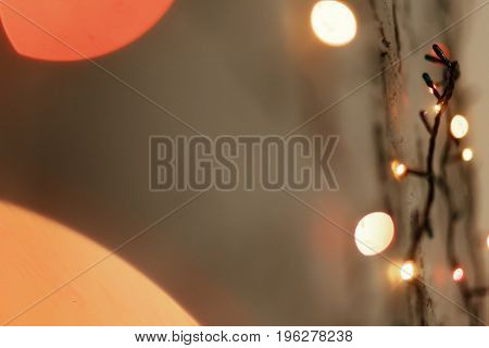 Warm Christmas Lights With Bokeh On Grey Wall. Colorful Garland Illumination. Space For Text. Season