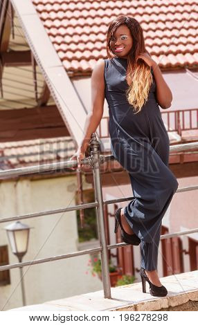 Black woman with overweight in a sexy trousers suit leaning against a railing