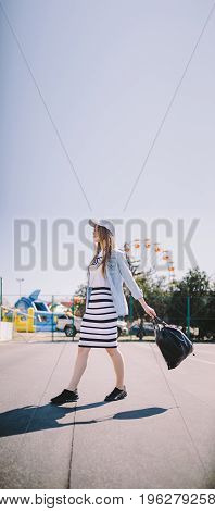 Portrait of beautiful stylish young woman with black bag against ferris wheel