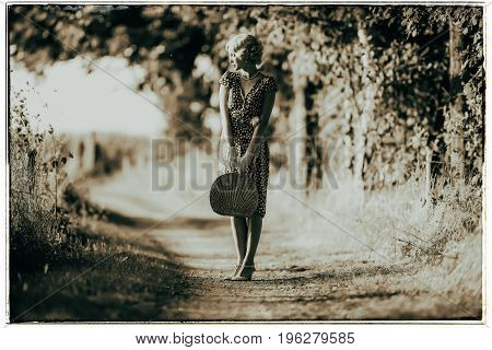Classic Black And White Photo Of 1920S Fashion Woman Standing With Handbag On Rural Pathway.