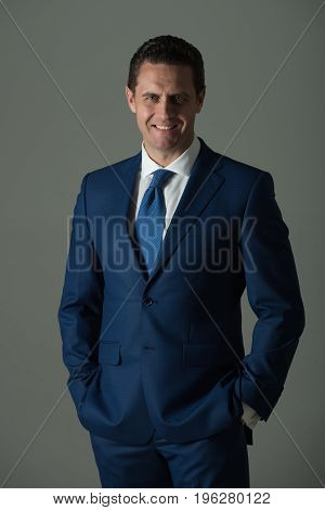 Happy Man Smiling With Hands In Pockets In Blue Suit