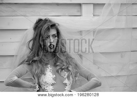 fashion woman with long hair in wedding dress and bride veil on wooden background black and white