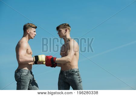 Sport people or team work. twins with muscular body. Boxer workout and healthy fitness. Man and coach sunny outdoor on blue sky. Winner and loser in boxing gloves.