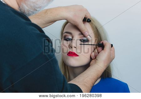 Visagiste applying black mascara on woman eyelashes with makeup brush. Girl with red lips on cute face and long blond hair on white background. Beauty salon. Visage make up cosmetics and skincare
