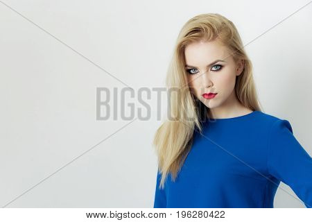 Woman with red lips on cute face posing in blue dress. Pretty girl young model with bright makeup and long blond hair isolated on white. Fashion make up visage cosmetics. Beauty salon copy space