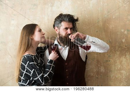 Girl with glass and man drinking wine from bottle. Woman with long hair and bearded hipster with messy haircut on beige wall. Couple in love. Alcohol and convive. Unhealthy lifestyle. Bad habits