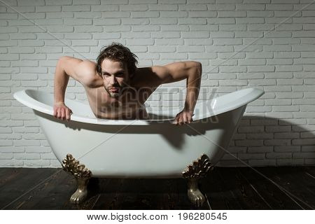 bathroom and home comfort. hygiene and healthcare. man with muscular body in bath. spa and relaxation. guy sitting in bath tub.