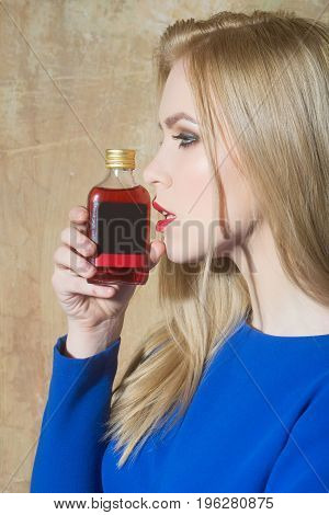 Girl posing with bottle of red liqueur. Pretty woman with blond long hair and fashionable make up in blue dress on beige wall. Alcohol and appetizer. Bad habits and unhealthy lifestyle