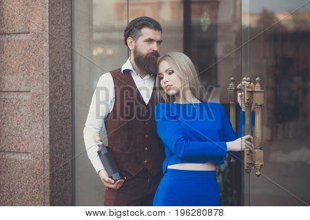 Boyfriend With Bottle Of Wine Hugging Girlfriend At Glass Door