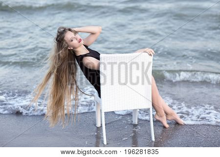 A beautiful female touching her long dark blonde hair resting on a big white chair. An elegant young lady sitting on a bright blue sea background. Leisure, relax, peace concept.