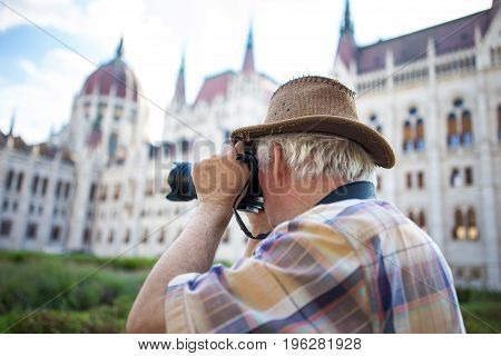 Senior pensioner photographing Parliament Building Budapest Hungary