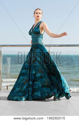 Full-length portrait of an attractive woman in a long waving emerald dress on a blue sky background. Beautiful girl in a long green dress, that flutters in the wind. A concept of femininity, harmony.