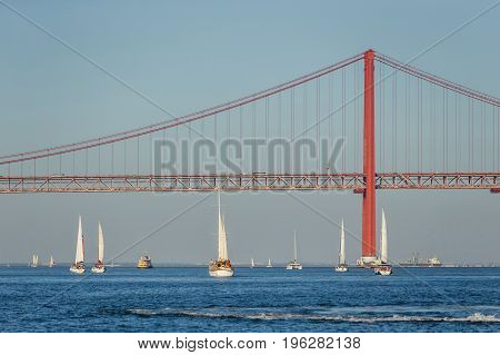 Boats sailing in river Tagus with bridge in Lisbon Portugal