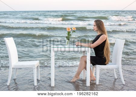 A thoughtful confident female sitting next to the white standing on a beach. A woman relaxing on a blue ocean background. An ideal lady in a saturated black dress. A girl with beautiful long hair.