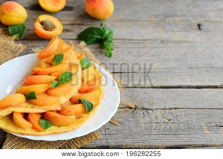 Summer apricot omelette. Omelette stuffed with fresh apricot slices and mint leaves on a white plate and a vintage wooden background with empty space for text. Beautiful breakfast idea