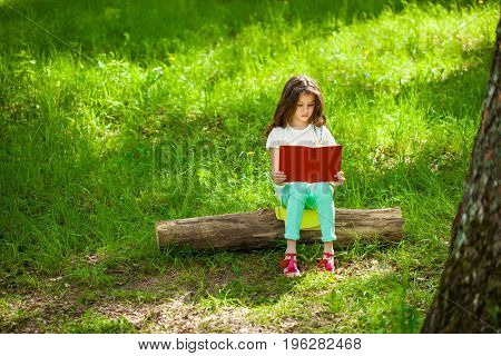 Charming little girl in forest with book on the background of summer park