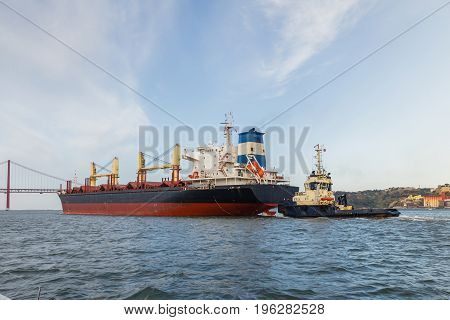 Big cargo ship in river being tugged