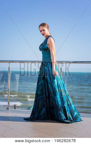 A gorgeous and young woman in a turquoise dress is posing at a glass balcony on a sea background. Fashionable and elegant lady in silk dress near summer beach. An attractive girl on a sea background.