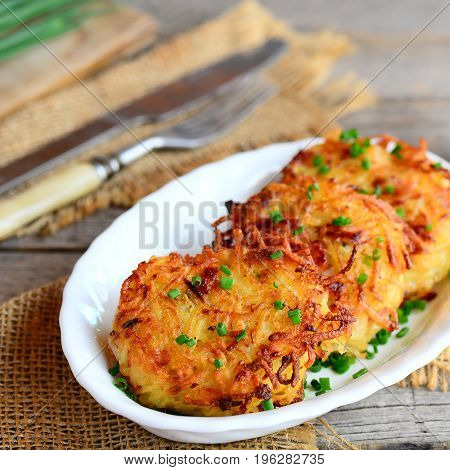 Crispy golden potato cutlets with ham and green onions on a white plate. Easy potato cutlets recipe. Rustic style. Closeup