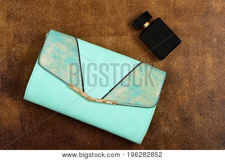 Blue Clutch And Perfume Bottle. Fashion And Scent Concept
