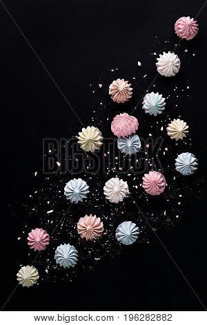 Colorful meringues on dark table. Many sweet zephyrs on black background. Pink, green, blue and white meringues top view.