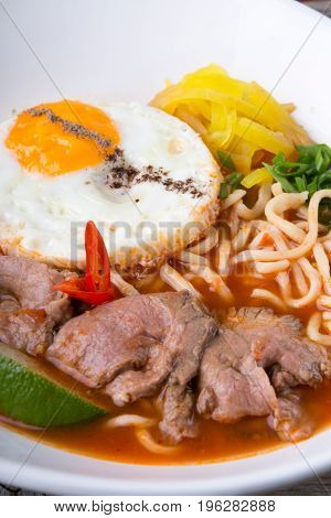 Asian noodles soup with fried egg and beef