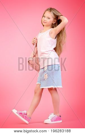 Children's fashion. Cute eight year old girl wearing summer jeans clothes and a bag posing over pink background. Studio shot.