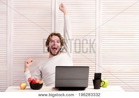 Guy with happy face and smile sits at his desk near laptop and apples. Bearded man with fruit and gadgets on light striped background. Home work concept. Man at working place with cellphone in tea cup