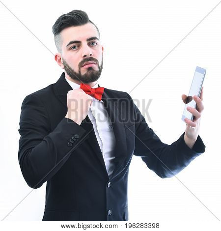 Businessman with beard and red bow tie and serious face holds black shiny tablet isolated on white background. Concept of importance style and business