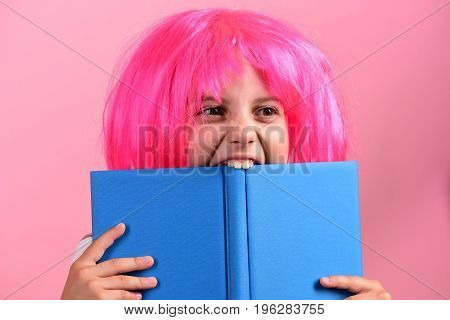 Girl Bites Big Blue Book. Pupil With Pink Wig.