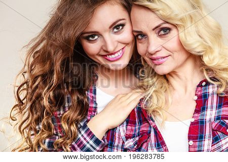 Generation and relationship. Portrait adult daughter with mother. Two gorgeous casual style women long hair blonde mom and brown haired girl studio shot