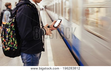 Young man waiting on station platform with backpack on background electric train using phone. Tourist text message and plan route of railway, railroad transport