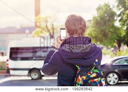 Travel man makes a photo or texting message on smartphone mobile closeup, travel sights of the city, architecture landscape on background; finger touch screen cellphone mockup nature