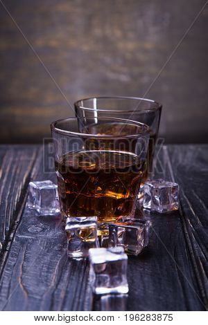 two glass with old whisky and ice on black background