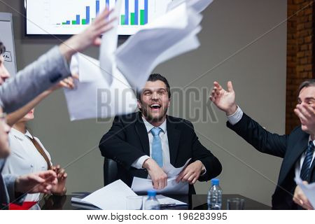 Business people sitting at table and throwing up papers and laughing.