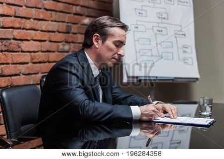 Side view of serious businessman in formal suit sitting at workplace and signing contract.