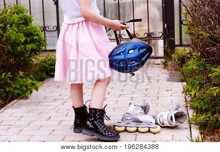 Girl is holding a helmet for roller skating in a pink fluffy skirt, at the feet lie roller skates. The concept of a daring, energetic girl, sport and healthy lifestyle